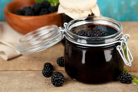Tasty blackberry jam and fresh berries, on wooden table photo