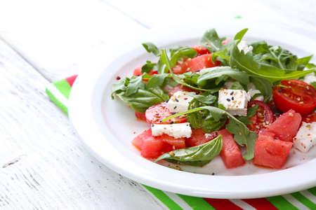 수 박, 토마토, 죽은 태아, arugula와 바 질 잎 샐러드 나무 배경에 접시에