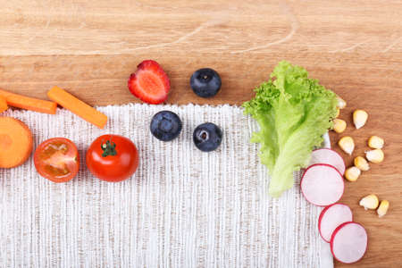 Different slices of vegetables and berries on wooden table photo