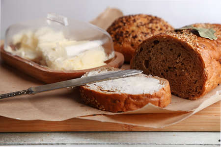 Baked bread and toast with fresh butter, on cutting board, on wooden background photo
