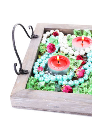Candles on vintage tray with decorative beads, stones, isolated on white photo
