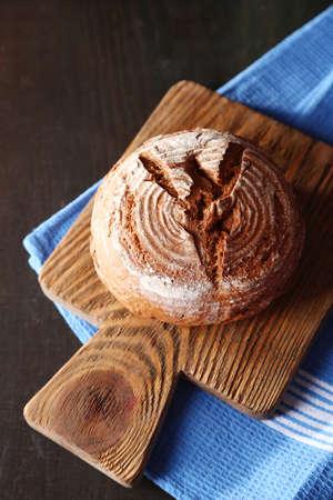 Fresh bread on dark wooden background photo