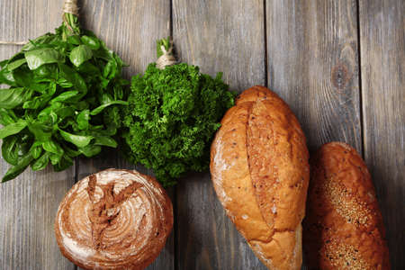 Fresh baked bread and fresh herbs, on wooden background photo
