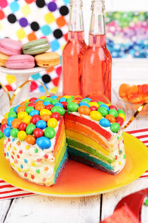 Delicious rainbow cake on plate on table on bright background photo