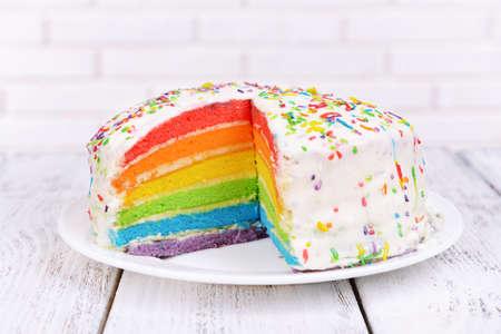 Delicious rainbow cake on plate on table on light background Standard-Bild