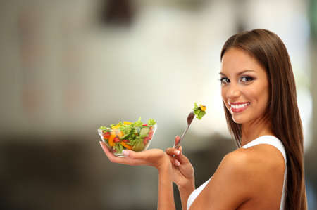 Beautiful young woman with salad on interior background