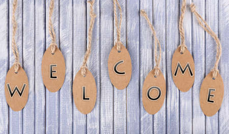 Welcome tags on wooden background photo