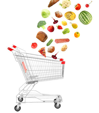 Products falling in shopping cart, isolated on white photo