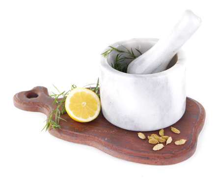 Estragon with lemon and cardamom in mortar pounder on cutting board isolated on white photo