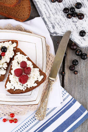 pone: Bread with cottage cheese and berries on plate close-up