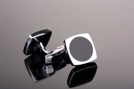 cuff links: Pair of cuff links on dark grey background
