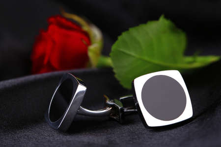 cuff links: Pair of cuff links with red rose on black silk fabric background