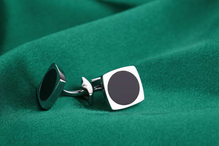 cuff links: Pair of cuff links on green silk fabric  background
