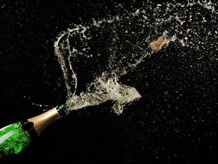 botella champagne: Salpicaduras de champán en fondo negro Foto de archivo