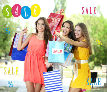 Concept of discount. Beautiful young woman with shopping bags at park photo