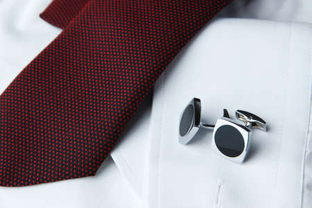cuff links: A pair of cuff links on a sleeve of the white shirt and a cravat near it Stock Photo