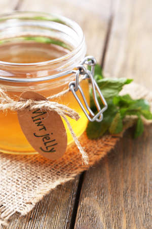 Homemade mint jelly in glass jar, on wooden background photo