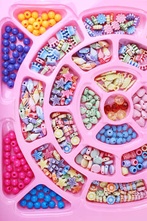 beading: Multicoloured beading kit for children in a pink box  Stock Photo