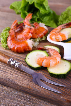 Fresh boiled prawns with lettuce and avocado on a wooden rectangular cutting board on wooden background photo