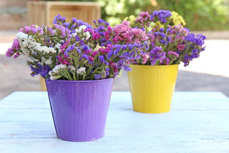 Beautiful flowers in flowerpot on wooden table, outdoors photo