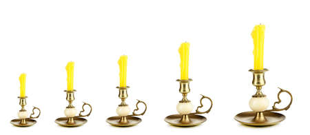 Evolution concept.Old candle holders with candle isolated on white photo