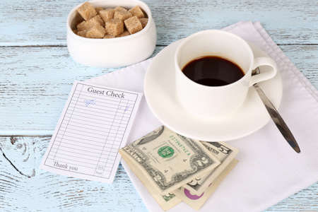 Check, money and cup of coffee on table close-up photo