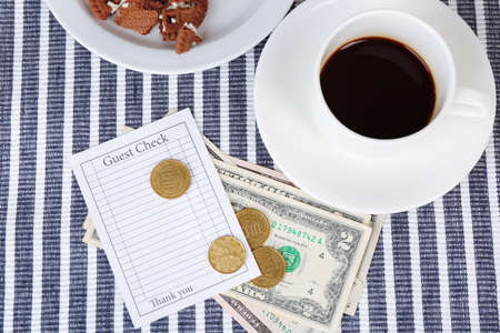 Check, cup of coffee and money on table close-up photo
