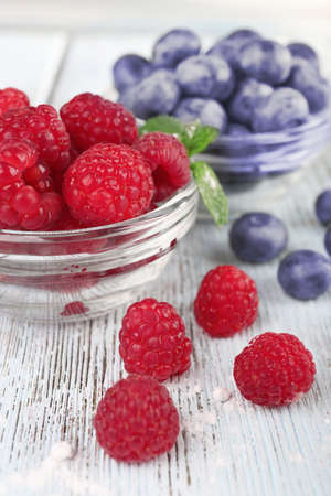 Glass bowls of raspberries and blueberries on wooden table on light background photo