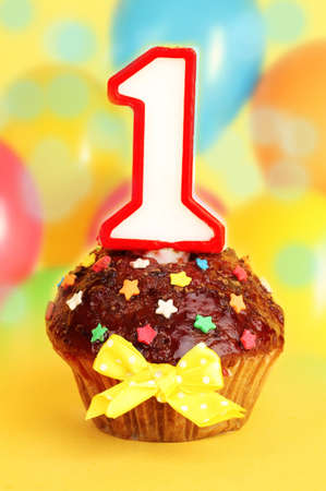 Birthday cupcake with chocolate frosting on bright background photo