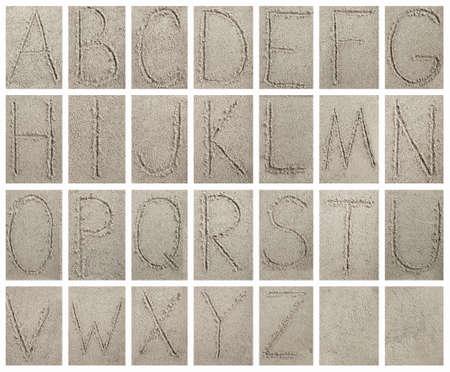 Handwritten alphabet letters on sand background photo