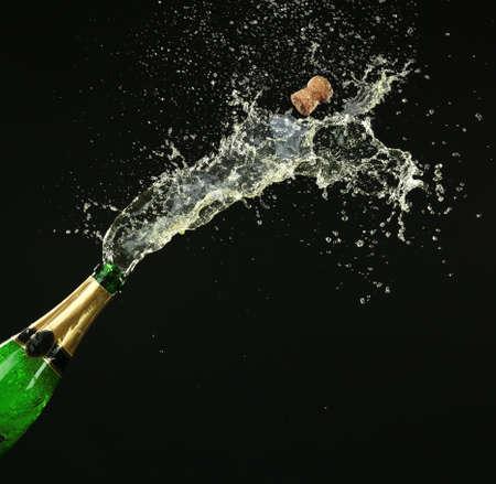 botella champagne: Botella de champagne con salpicaduras sobre fondo negro