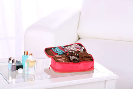 Handbag with accessorises and perfumes in bottles on table on  home interior background photo
