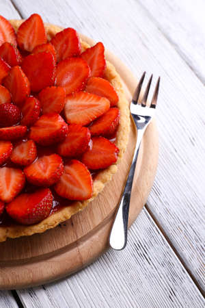 Strawberry tart on color wooden background photo