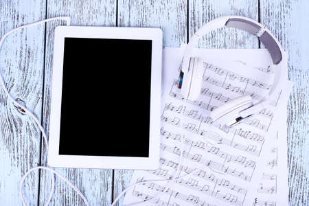 Tablet, printed music and earphones on wooden background photo