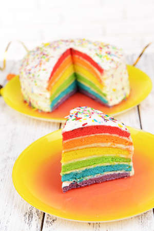 Delicious rainbow cake on plate on table on light background photo