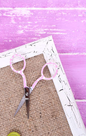 brads: Scrapbooking craft materials and wooden frame with sackcloth inside on color wooden background Stock Photo