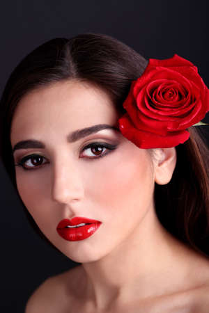 Girl with red lips and rose on dark background photo