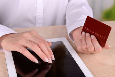 Female hands holding credit card and computer tablet on table on close up photo