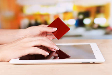 Female hands holding credit card and computer tablet on table on bright background photo
