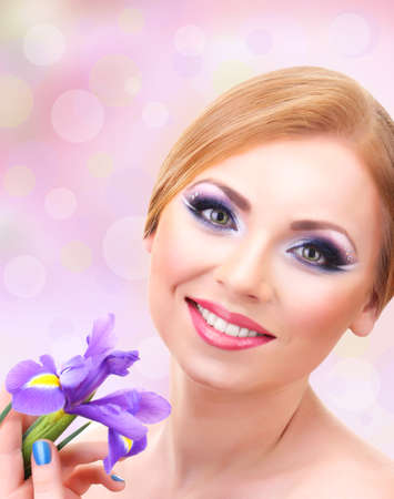 Beautiful young woman with glamour make up and flower ob bright background photo