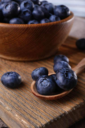 Wooden bowl of blueberries on cutting board on wooden background