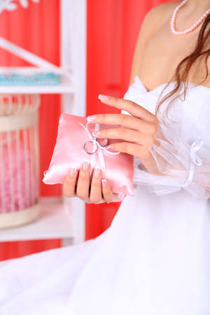 wrist cuffs: Bride in white dress and gloves holding decorative pillow with wedding rings, close-up, on bright background