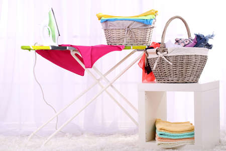 Baskets with laundry and ironing board on light home interior background