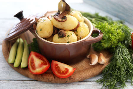 Young boiled potatoes in pan with vegetables on wooden table, close up photo