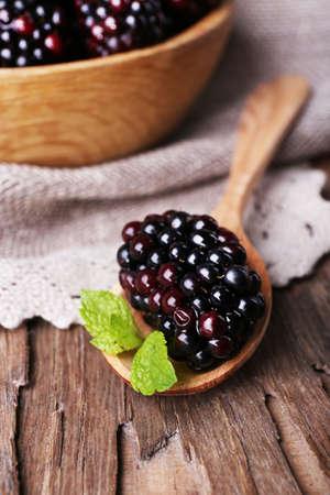 bawl: Wooden bowl of blueberries on sacking napkin on wooden background closeup Stock Photo