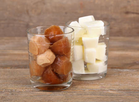 Iced coffee and milky cubes in glass on wooden background photo