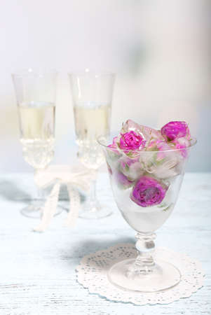 Ice cubes with rose flowers in glass bowl and two glasses with champagne on wooden table, on light background photo