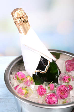 Frozen rose flowers in ice cubes and champagne bottle in bucket, on light background photo