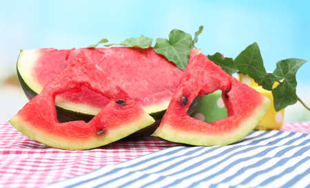 Fresh slices of watermelon on table, on blue background photo