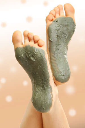 foots: Woman foots with cosmetic clay on bright background